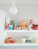 Detail of crockery and storage jars on white wall-mounted shelves behind spherical ceiling lamp