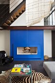A deep blue fireplace and zebra rug are the attention getters in this modern living room