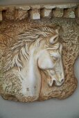 Stone relief of horse head on lilac-painted wall