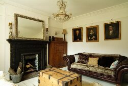 Masculine lounge with open fireplace and dark leather sofa; gilt-framed oil paintings on wall in elegant, rustic atmosphere