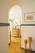 View of rustic chest of drawers in foyer through arched doorway in traditional apartment