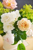 Bouquet of variously coloured roses on table