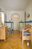 Pale wood bench and chest of drawers in hallway with fishbone parquet floor and arched doorways