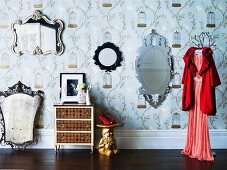 Collection of antique mirrors on patterned wallpaper as a background for red pumps on a table made from a garden gnome painted gold and red evening dress on a clothes hanger on a clothes stand