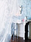 A veiled peek through a half closed voile curtain of a romantic dressing table ensemble in front of floral wallpaper