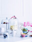 Pastel and antique style white porcelain, cake stands with glass covers and pink aperitif glasses and colorful cups on a white table