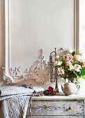 Bouquet of roses and embroidered pale fabric on chest of drawers delicately painted in soft colours below white wooden wall panel with ornate carved details in elegant, country-house style