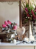 Bouquets in silver-plated vases and crystal goblet on shelf in front of mirror in elegant atmosphere