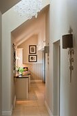 Sunlit hallway with view of kitchen unit in open-plan attic in elegant country-house style