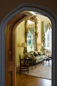 View into grand living area with Baroque wall-mounted mirror, upholstered sofa and standard lamps