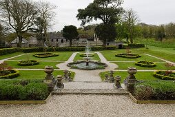 English gardens with central fountain and traditional stately home in background