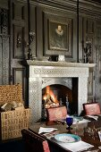 Roaring open fire and festively set dining table in dining room of English stately home with dark wood panelling
