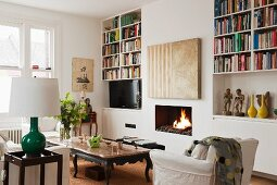 Modern painting over a fireplace, open bookshelves, marble top coffee table and white armchair in a living room