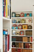 Open shelves with a collection of English Royal Family memorabilia and antique books