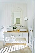 Solid wooden washbasin in country style with a hanging, framed mirror and round wash bowls; in between white orchids