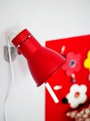 Small, red, adjustable wall lamp in front of detail of artistically decorated wall