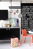 Young, hip kitchen design with large, black and white lettering on the wall, hanging pots and bright orange plastic chair