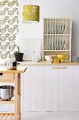 Simple country kitchen in white with plate rack and lamp and curtain made from 70's style fabric. In the foreground a work area made of natural beech.