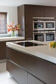 Kitchen island and fitted appliances in designer kitchen with brown cupboard doors