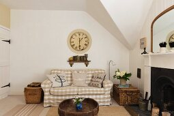 Sitting room with a white and beige gingam sofa (Ektorp from Ikea) wooden Afghan coffee table and a large Cafe de Marguerites wall clock