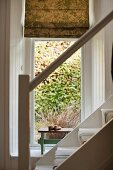 View through stair bannister to panelled window alcove