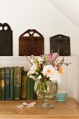 Camelia and roses in glass vase on wooden tabletop with vintage books