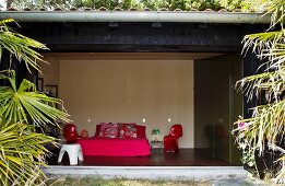 View from the garden into a modern bedroom with designer chairs and a double bed in eye popping colors