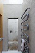 Contemporary towel rack on a raw concrete wall in a minimalist bathroom