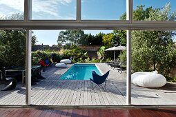 View through an open terrace door onto a large wooden terrace with a pool and designer furniture