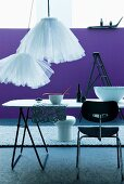Simple dining table and contemporary tulle lampshades in front of purple wall and grey long-pile rug
