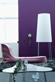 Contemporary living room with designer coffee table, couch and standard lamp against purple wall