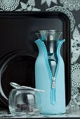 Glass carafe in light blue neoprene jacket in front of black tray against floral wallpaper