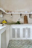 Corner of Moroccan kitchen with pale tiled worksurface, white base units with perforated wooden doors, floral grey and white stone floor and curved brackets supporting crockery shelf on two walls