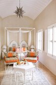 Bright, Oriental bedroom with white side table and set tea tray; ornate metal chairs with orange and beige cushions for taking afternoon tea