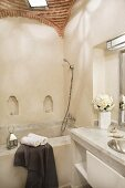 Corner of Oriental bathroom with vaulted brick ceiling and tealights in small arched niches; bathtub and washstand clad in pale stone slabs