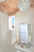 Spherical pendant lamp hanging from vaulted brick ceiling above simple washstand with mirror in Oriental bathroom; view through small window