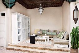 Oriental-style loggia with floor cushion sofas and modern table on raised platform; magnificent wooden ceiling and silver, ornate pendant lamp created by skilled craftsmen