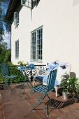 Afternoon tea on sunny terrace with reupholstered antique sofa and delicate blue, vintage-effect garden furniture