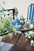 Unusual, antique teapots on silver tray on blue-painted garden chair; terrace with floral balustrade