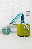 Blue towel on white lounger in front of white curtain; bikini on green, cubic pouffe in foreground