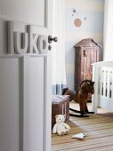 View into nursery with nostalgic atmosphere; white cot, rocking horse and small cupboard with roof against wall painted with pale blue and white stripes and circles