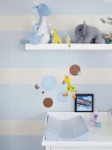 Nursery wall decorated with pale blue stripes and circles; various soft toys on floating shelf and pale blue changing mat on white changing unit