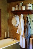 Vintage bathroom in earthy, natural shades with old enamel pots and simple dressing gowns above built-in bathtub