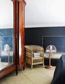 Large, antique mirrored cupboard with exotic wood veneer next to simple wicker chair and fan