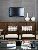 White vases on brown and black sideboard and flat-screen TV on grey wallpapered wall; two elegant armchairs with woven backs in foreground