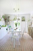 White dining set in sunny kitchen-dining room with cheerful floral flooring and green accents
