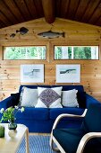 Comfortable, electric blue sofa and armchair in simple wooden house; two window slits and angling trophies above sofa