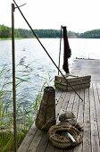 Fishing utensils on old wooden jetty next to idyllic lake