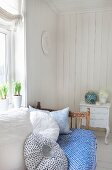 Vintage daybed with blue and white throw and soft cushions below window in sunny room