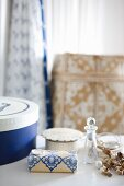 Decorative soap, pots and small crystal bottle on white surface